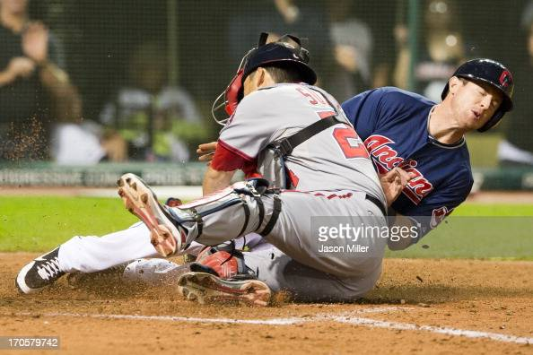 Drew Stubbs of the Cleveland Indians slides into catcher Kurt Suzuki of the Washington Nationals to score the gamewinning run in the ninth inning at...