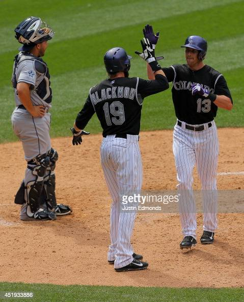 Drew Stubbs of the Colorado Rockies celebrates his two run home run with Charlie Blackmon as catcher Yasmani Grandal of the San Diego Padres looks on...