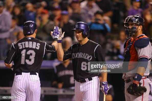 Drew Stubbs of the Colorado Rockies is congratulated by David Hale after his solo home run during the second inning as catcher AJ Pierzynski of the...