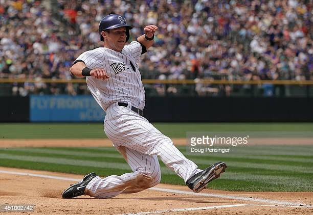 Drew Stubbs of the Colorado Rockies slides home to score on a single by Justin Morneau of the Colorado Rockies off of starting pitcher Wily Peralta...