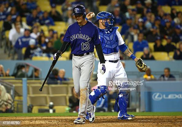 Drew Stubbs of the Colorado Rockies walks back to the dugout after striking out swinging in the eighth inning as catcher Yasmani Grandal of the Los...