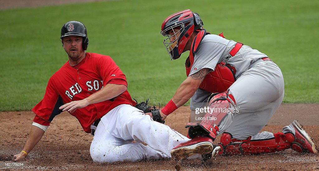Drew Sutton #44 of the Boston Red Sox is tagged out at home by catcher Tony Cruz #48 of the St. Louis Cardinals in the second inning during the game at JetBlue Park on February 26, 2013 in Fort Myers, Florida.