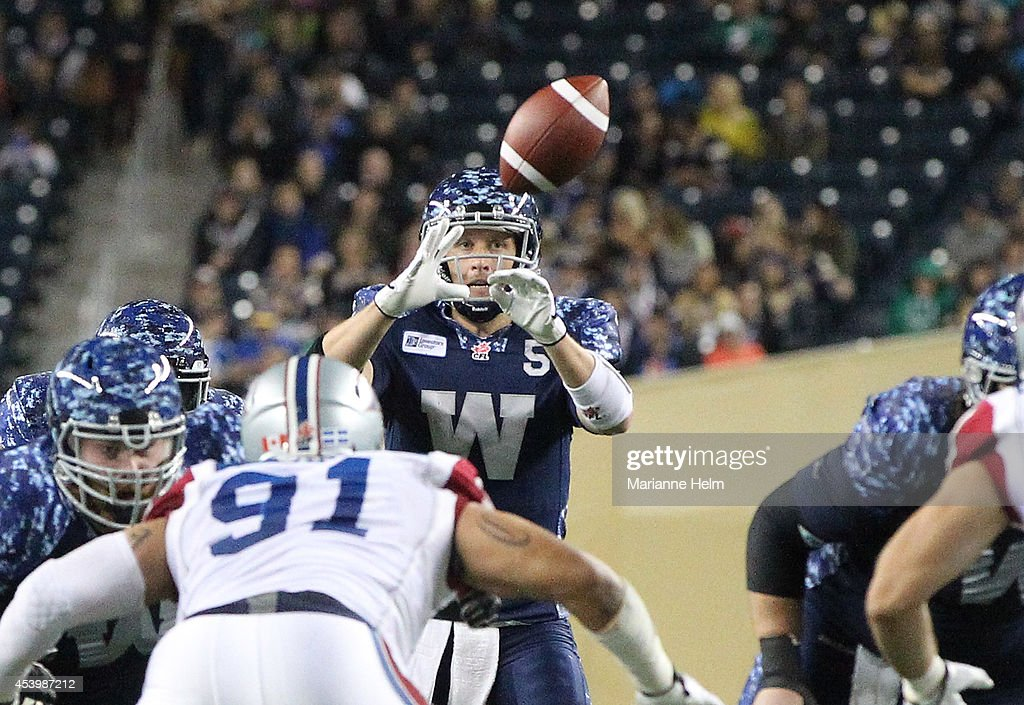Drew Willy #5 of the Winnipeg Blue Bombers prepares to grab the snap in second half action in a CFL game against the Montreal Alouettes at Investors Group Field on August 22, 2014 in Winnipeg, Manitoba, Canada.