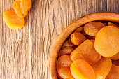 Dried apricots, dried fruits in a wooden plate. Rustic style. Healthy diet. Place for text. Kaisa.