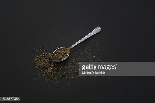 Essiccato cucchiaino di basilico in metallo sul tavolo di legno scuro : Foto stock