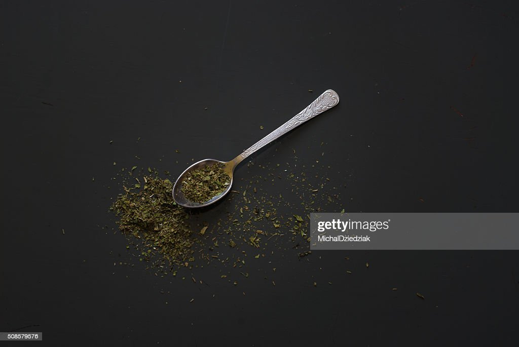 Dried basil on metal teaspoon on dark wooden table : Stock Photo