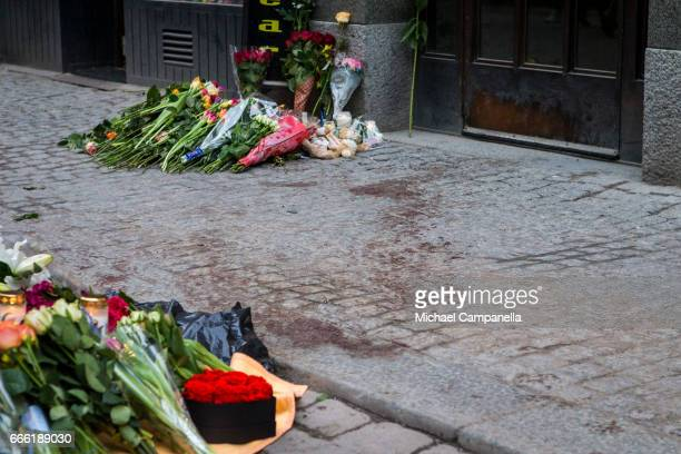 Dried blood remains on the pavement on Drottninggatan at the scene of the terrorist truck attack in downtown of the city where sympathy flowers are...