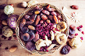 dried fruit like figs,cranberries,datesand apricots in rustic basket on wooden background, decorated with baubles and sugar cane, healthy snack in christmas time