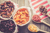 Overhead shot of dried fruits in paper bag on an old wooden table