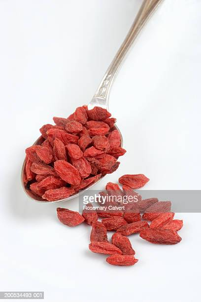 Dried goji berries on spoon, against white background, close-up