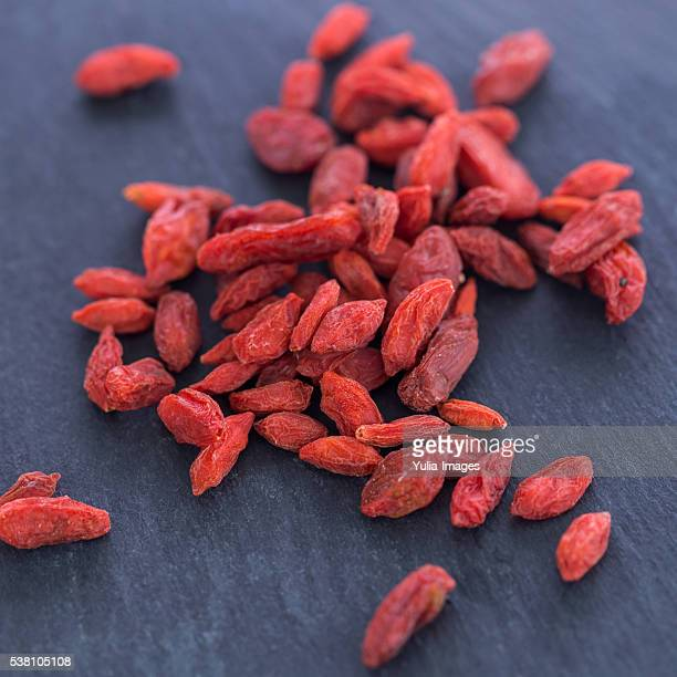 Dried Goji Berries Scattered on Textured Surface