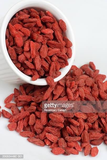 Dried goji berries spilling from bowl, against white background