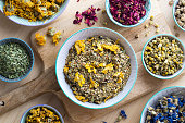 Dried herbs in bowls on a wooden table, top view. Calendula, rose petals, nasturtium seeds, plantain, chamomile, mullein, cornflower.
