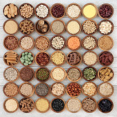 Dried macrobiotic super food with legumes, seeds, nuts, cereal, vegetables, grains and whole wheat pasta with foods high in protein, omega 3, anthocyanins, antioxidants, minerals and vitamins on rusti
