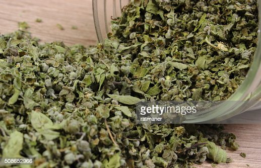 Dried marjoram spilling out of glass jar. Wooden background : Stock Photo