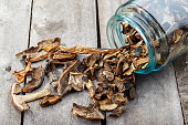 Dried mushrooms in a jar, sliced dried boletus on a wooden background