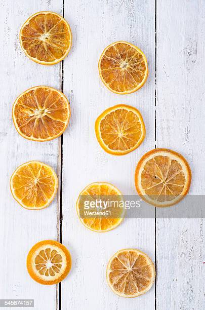 Dried orange slices on white wood