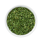 Dried Parsley Flakes in a Ceramic Bowl. The image is a cut out, isolated on a white background, with a clipping path.