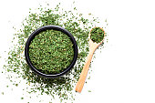 Spices: Top view of a black bowl filled with dried parsley isolated on white background. A wooden spoon is beside the bowl and dried parsley is scattered on the table. Predominant colors are white and