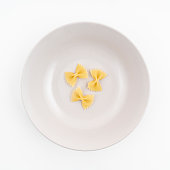 Three pieces of dried butterfly format pasta on the plate