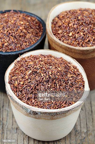 Dried rooibos tea in small wooden pots
