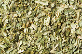 Close up dried chopped tarragon leaf spices texture background