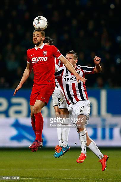 Dries Wuytens and Stijn Wuytens of Willem II are beaten to the header by Luc Castaignos of Twente during the Dutch Eredivisie match between Willem II...