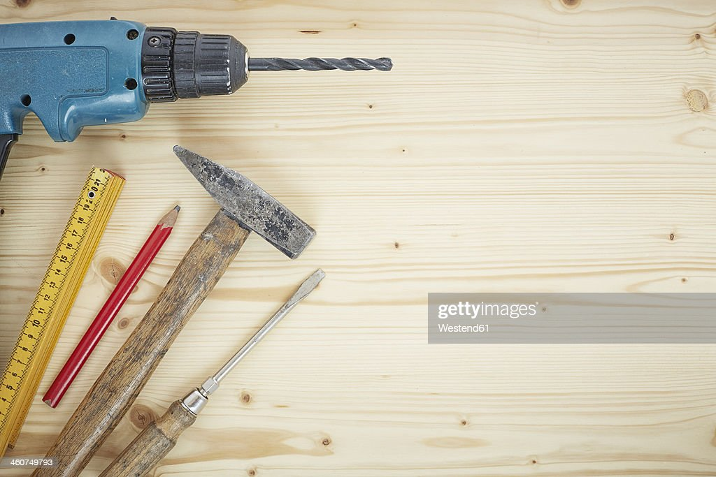 Drill, pencil, hammer, screwdriver, folding ruler on wood, close up