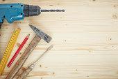 Drill, pencil, hammer, screwdriver, folding ruler on wood, close up