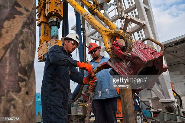 Driller Adrian Vallarta left and floor hand Jose Garza attach a drill screen to the elevator on Orion Drilling Co's Perseus drilling rig near Encinal...