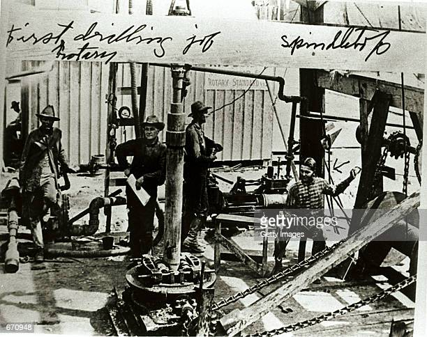A drilling crew takes a break atop Spindletop Hill in Beaumont Texas where the first Texas oil gusher was discovered January 10 1901 The writing on...