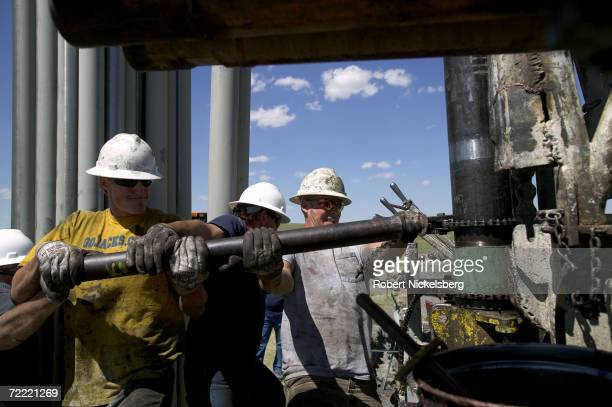 Drilling hands tighten 10' metal pipe casing that will be connected and fitted into a drilled coal bed methane well for natural gas extraction on...