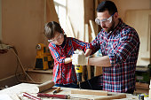 Little boy helping his father drill wooden plank together
