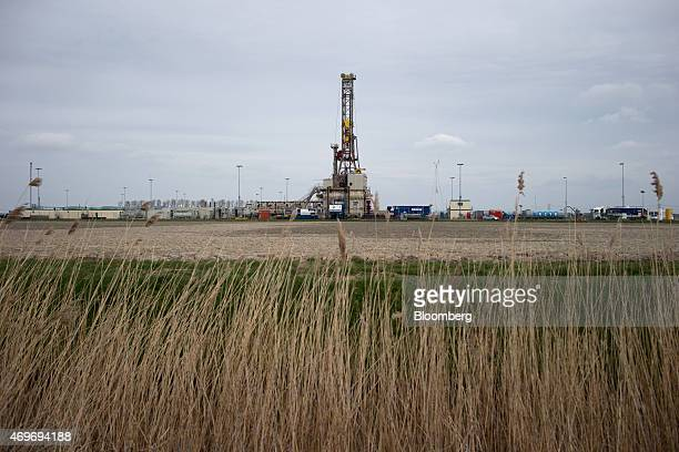 A drilling rig stands above natural gas extraction machinery and pipework at an onshore site operated by Nederlandse Aardolie Maatschappij BV in the...