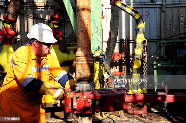 Drilling rig worker wearing a white hard hat and safety gear