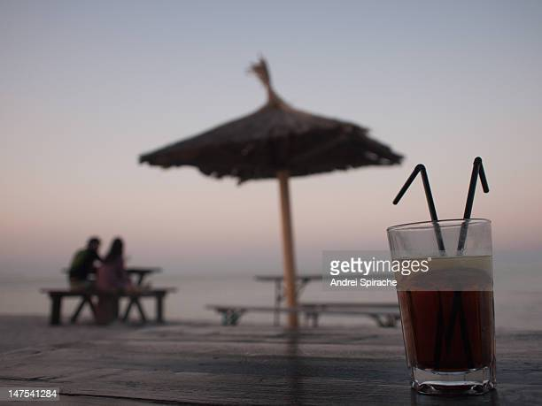 A drink and a couple on the beach at sunset