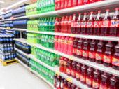 Drink bottles on display on shelves in a supermarket blur background
