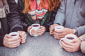 Close up of hands holding cups with hot wine at outdoor cafe on a street, christmas market.  Vienna, Austria.