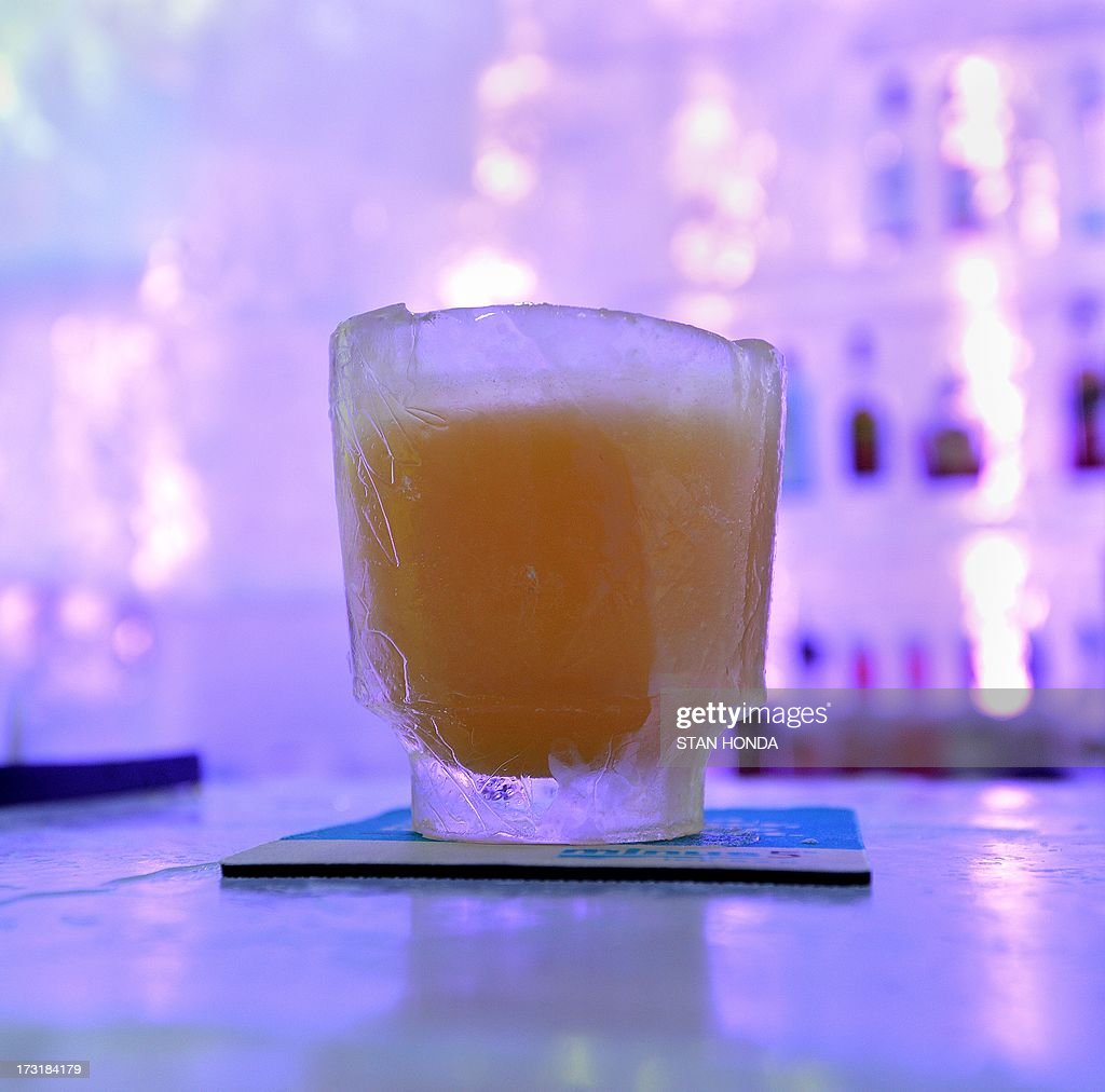 A drink in the Minus 5 Ice Bar during a preview at the New York Hilton Midtown Hotel July 9, 2013 in New York. The bartender said guests must use coasters under the drinks to prevent the glass from sticking to the ice surfaces. The bar is constructed of 90 tons of ice and is kept at a temperature of -5 degrees C (23 degrees F). Guests are given parkas, gloves and hats and for an additional fee, fur coats. Designs in the wall and around the bar are carved by ice sculptor Peter Slavin. AFP PHOTO/Stan HONDA