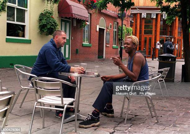 Drinkers sitting at a table outside a bar in Canal Street Manchester a famous gay district of the city
