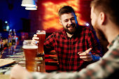 Man drinking beer and laughing with his friend