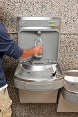 """""""A male hand is filling a disposable water bottle from a drinking fountain filling station. Gaining popularity, systems like this allow people to easily refill water bottles with filtered water, rathe"""