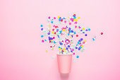 Drinking Paper Cup with Multicolored Confetti Scattered on Fuchsia Background. Flat Lay Composition. Birthday Party Celebration Kids Fun Cheerful Atmosphere. Greeting Card Poster Template