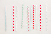Different drinking straws over white background. Top view, blank space