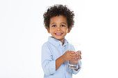 little boy with a glass of water smiling isolated on white background