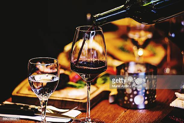 Drinking Water By Bottle Pouring Wine In Glass On Table