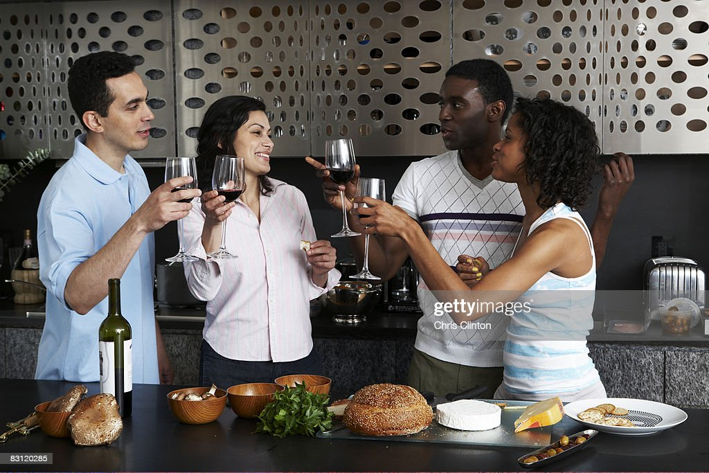 Drinking wine while preparing meal in kitchen : Stock Photo