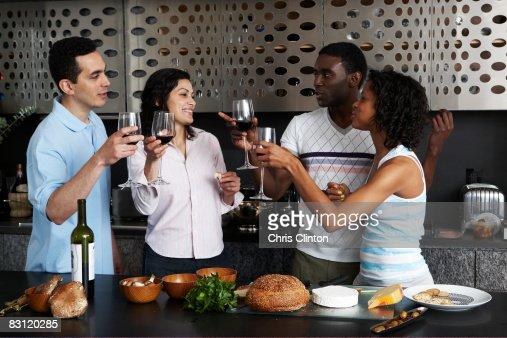 Drinking wine while preparing meal in kitchen : Bildbanksbilder