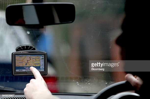 A driver adjusts his TomTom navigation system on a vehicle windscreen in London UK on Monday Feb 23 2009 TomTom NV Europe's largest maker of...