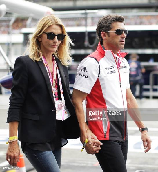 Driver and actor Patrick Dempsey walks past the Infiniti Red Bull Racing garage with his wife Jill Fink before the German Grand Prix at...